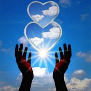 2 white Reiki hearts above hands held up to sky